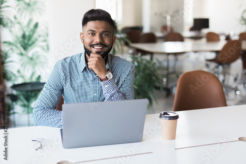 Fototapeta Young indian man smiling and working at modern office obraz