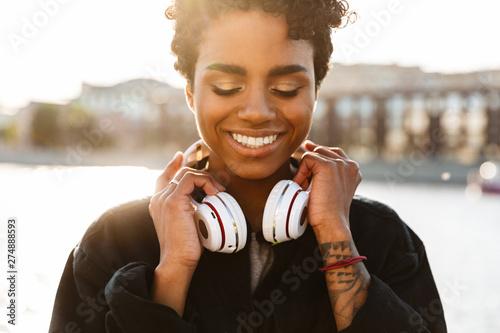 Obraz Portrait of joyful african american woman holding headphones while walking along riverfront - fototapety do salonu