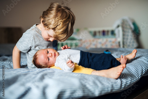 A small boy with a newborn baby brother at home. Canvas Print