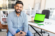 Young Indian Business Man Working On Laptop In Modern Office