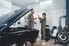 Caucasian Couple Hanging Out In A Garage, Fixing An Old Retro Vintage Car