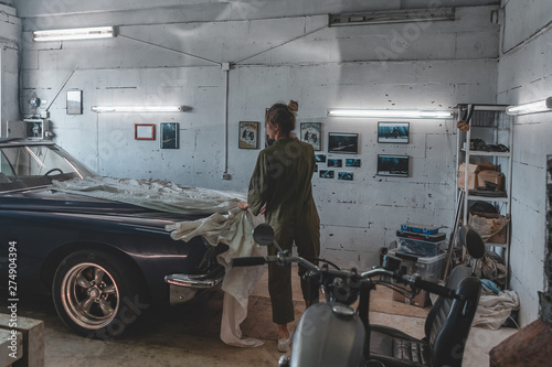 Attractive Caucasian female removing cover from her vintage old car in a garage