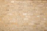 Fototapeta Kamienie - Old beige brick wall background texture close up