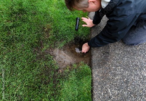 Obraz Sprinkler system being repaired by mature man with irrigation parts laying on ground - fototapety do salonu