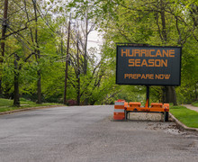 Digital Electronic Mobile Road Sign That Says Hurricane Season Prepare Now, On The Side Of A Tree Lined Road