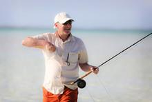 Older Man Bone Fishing In The Bahamas Walking Through The Water.