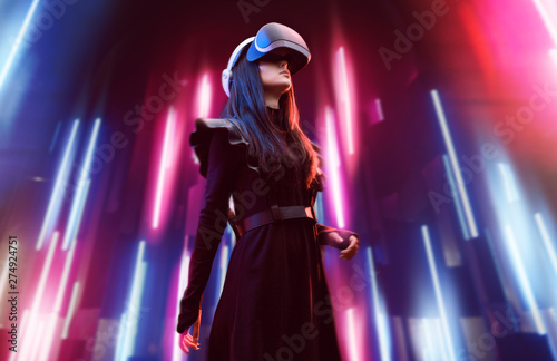Beautiful woman in futuristic dress over dark background. Girl in glasses of virtual reality. Augmented reality, game, future technology, robots and people concept. VR. Neon light.