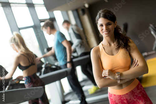 Poster Fitness Smiling sporty young woman standing with arms folded and looking at camera at the gym