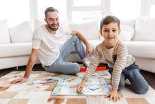 Cheerful Young Father Playing Monopoly