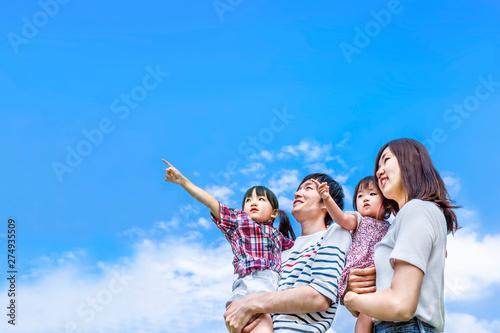 Fotografia  青空をバックに遠くを見つめ指さす4人家族。幸せ、希望、愛情、育児イメージ