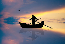 Fisherman On The Boat At Sunset
