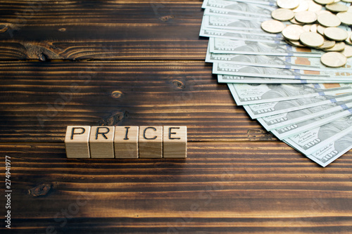 Fotografía  inscription price wooden cubes with letters, money coins american dollars bankno