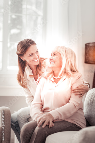 Beautiful mother and daughter smiling happily to each other Wall mural