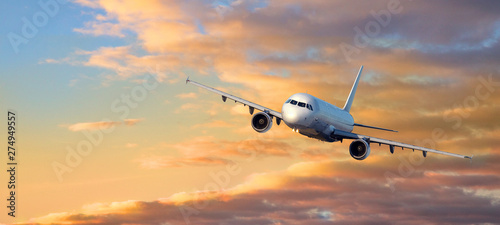 airplane fly at Sunset clouds