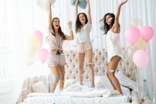 Yeah! Four Attractive Young Women In Pajamas Smiling And Gesturing While Jumping In The Bedroom With Confetti Flying Everywhere