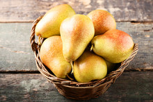 Ripe Pears In Basket On Grey Wooden Table