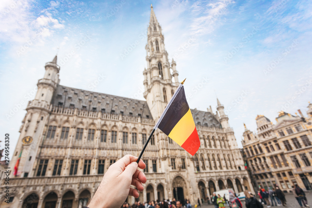 Fototapety, obrazy: Woman tourist holds in her hand a flag of Belgium against the background of the Grand-Place Square in Brussels, Belgium
