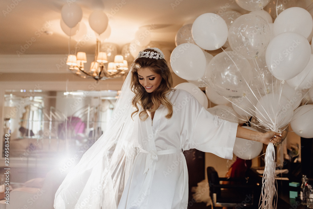 Fototapety, obrazy: Pretty Young Bride Model Holding Bunch of Balloons. Woman Wearing Gown, Looking Down and Keeping in Hand Helium Air Bubbles. Colorful Photo of Wedding Day. Hotel Apartment Interior on Background