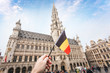 canvas print picture - Woman tourist holds in her hand a flag of Belgium against the background of the Grand-Place Square in Brussels, Belgium