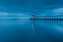 Still Water Long Exposure Image Of Stormclouds Pier And Lighthouse At Michigan City Indiana