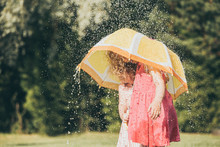 Two Young Girls Sisters Standing Outdoors In Garden Under Umbrella With Water Drops Falling, Sisters Smiling And Having Fun. Childhood Memories Concept. Vintage Instagram Look, Lifestyles.