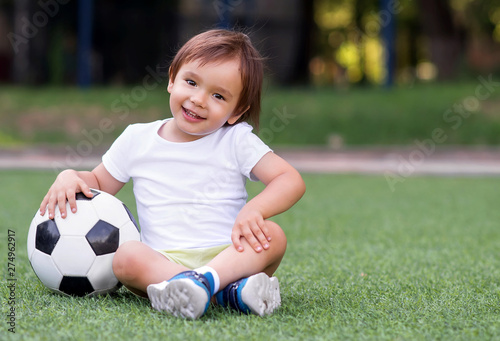 Little toddler boy sitting with legs crossed on football field in summer day with soccer ball Canvas Print