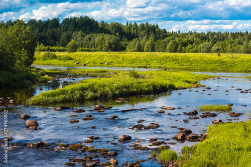 Beautiful view of the river in the countryside. The river flows among the fields and forests.