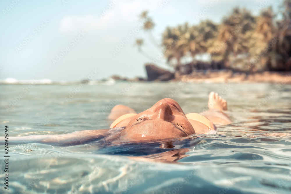 Fototapeta Woman relaxing and sunbathing meditating in tranquil sea beach palm trees travel tropical vacation lifestyle