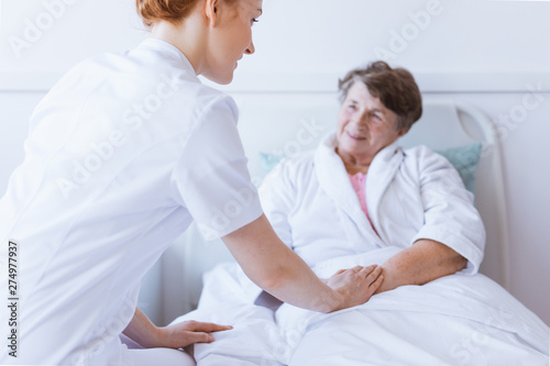 Poster Individuel Senior grey woman lying in white hospital bed with young helpful nurse holding her hand