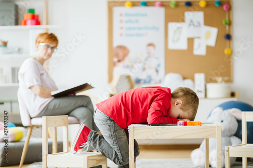Photo Cute little boy with ADHD during session with professional therapist