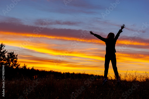 Fotografie, Obraz  Radosna kobieta na tle zachodu słońca