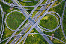 Aerial View Of Highway Junctions. Bridge Roads Shape Number 8 Or Infinity Sign With Green Garden And Trees In Connection Of Architecture Concept. Top View. Urban City, Taipei At Sunset, Taiwan.