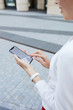 Mid section closeup of young businesswoman holding smartphone outdoors in urban area, copy space