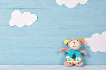 Cute toy puppy beanbag on a blue wooden background with white clouds, baby card
