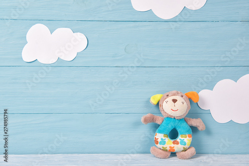 Poster Montagne Cute toy puppy beanbag on a blue wooden background with white clouds, baby card
