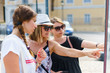 Three female tourist women looking at the map location on the info panel in the Corfu Town tourist destination in a summer day on the vacation holiday