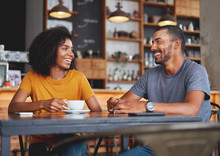 Happy Young Couple Sitting In Cafe