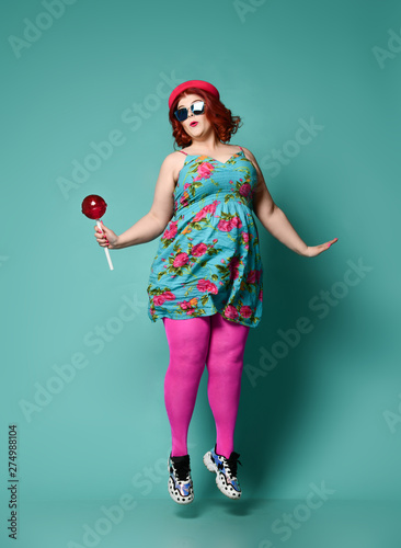 Funny overweight fat chubby woman in colorful hat, sundress and tights with extra big lollipop jumps like she is trying to fly