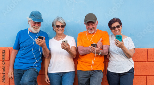 Valokuvatapetti Two couples of senior people standing against an orange and blue wall smiling and looking at the mobile phone using earphones