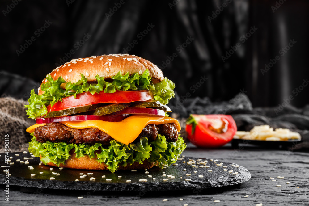 Fototapety, obrazy: Beef burger with cheese, tomatoes, red onions, cucumber and lettuce on black slate over dark background. Unhealthy food