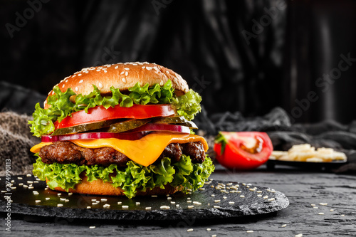 Fototapeta Beef burger with cheese, tomatoes, red onions, cucumber and lettuce on black slate over dark background. Unhealthy food obraz