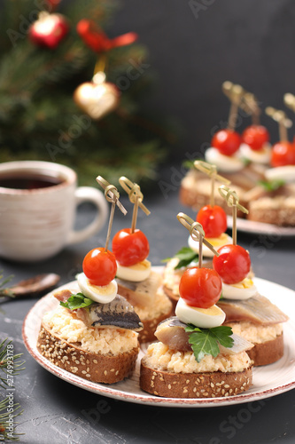 Canapes with salted herring, cheese, quail eggs and cherry tomatoes on rye crout Wallpaper Mural