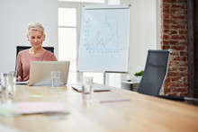 Portrait Of Smiling Female Boss Working In Office Sitting At Table In Conference Room, Copy Space