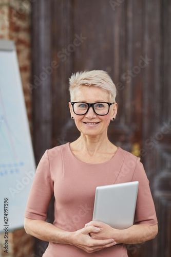 Waist up portrait of successful mature businesswoman wearing glasses smiling cheerfully at camera while posing in modern office