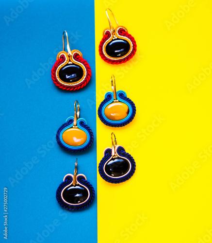 Kolorowe, modne kolczyki sutasz na żółto-niebieskim tle