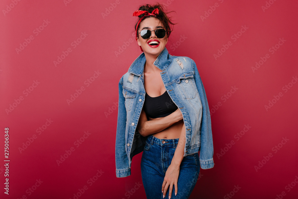 Fototapeta Pleased girl wears jeans laughing on claret background. Spectacular female model looking to camera through black sunglasses.