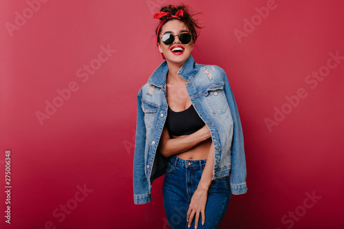 Fotografía Pleased girl wears jeans laughing on claret background
