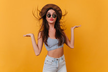 Lovable Tanned Girl In Trendy Summer Attire Dancing In Studio On Photoshoot. Indoor Photo Of Fascinating Brunette Female Model In Blue Tank-top And Brown Hat.