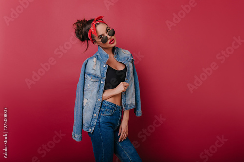 Fotografie, Obraz  Serious fashionable girl in denim outfit standing in confident pose