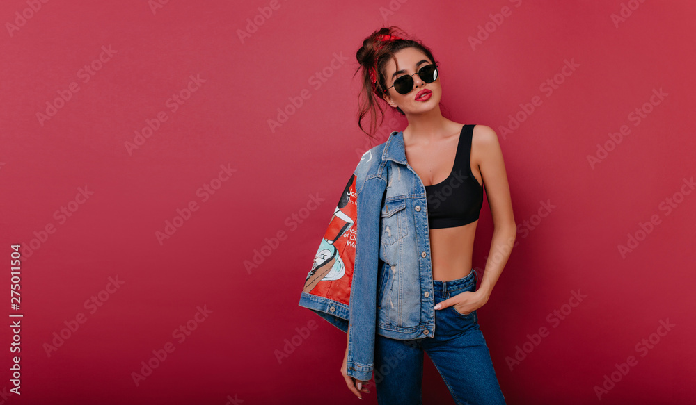 Fotografía Adorable tanned girl in black sunglasses standing in confident pose on claret background